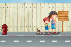 有他们的宠物的男孩在街道 免版税库存照片