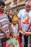 有他的家庭的一个年轻男孩在母牛GaijatraThe节日  免版税库存照片