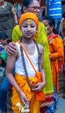 有他的家庭的一个年轻男孩在Gaijatra母牛节日  库存照片