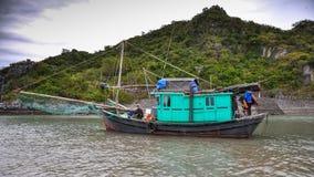 有他的家庭的渔夫在一个渔船,越南 库存照片