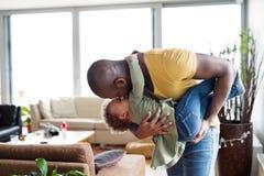 有他的小女儿的年轻美国黑人的父亲在家 库存照片