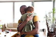 有他的小女儿的年轻美国黑人的父亲在家 免版税库存图片