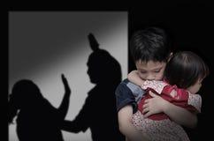 有他的战斗在背景中的父母的孩子 免版税图库摄影