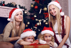 有他们的摆在圣诞树旁边的母亲的逗人喜爱的小女孩 库存照片