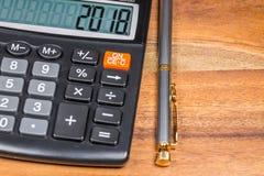 有2018的数字计算器和圆珠笔在木表上分支 关闭 免版税图库摄影