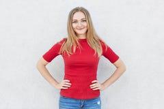 有轻的有头发和的蓝眼睛的高兴的女性在她的穿红色毛线衣和牛仔裤的面孔的微笑握在腰部Attracriv的手 免版税库存照片