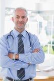 有他的横渡的胳膊的可爱的医生 库存图片
