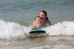 有他的母亲游泳的男孩在地中海 免版税库存图片