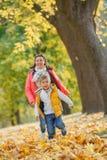 有他的母亲的可爱的男孩在秋天公园 免版税库存图片