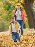有他的母亲的可爱的男孩在秋天公园 图库摄影