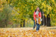 有他的母亲的可爱的男孩在秋天公园 免版税图库摄影