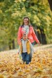 有他的母亲的可爱的男孩在秋天公园 免版税库存照片
