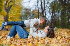 有他的母亲的可爱的男孩在秋天公园 库存照片
