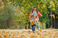 有他的母亲的可爱的男孩在秋天公园 库存图片