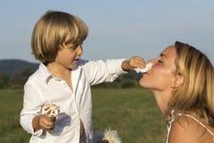 有他的母亲的年轻逗人喜爱的男孩,吃鲜美冰淇凌 库存照片