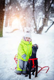 有他的沮丧朋友的小逗人喜爱的男孩在冬天森林里 库存照片