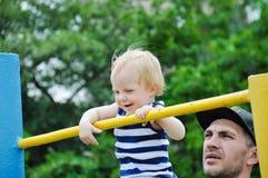 有他的演奏体育的父亲的小坚强的婴孩室外 在他的锻炼期间的孩子 免版税图库摄影