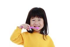 有去的牙刷的特写镜头逗人喜爱的亚裔女孩在手中掠过 免版税库存照片