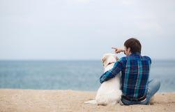 有他的狗的人在坐回到照相机的夏天海滩 免版税库存照片