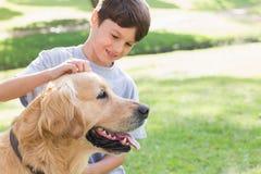 有他的狗的小男孩在公园 库存照片
