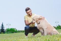 有他的狗的英俊的人 免版税图库摄影