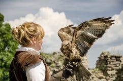 有他的猎鹰的年轻俏丽的以鹰狩猎者,用于猎鹰训练术, 库存照片