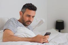有他的电话的性感的人在床上 库存图片