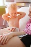 有他的看智能手机屏幕的母亲的一个岁男婴 免版税库存图片