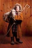 有他的职员的嬉戏的女孩牧羊人在他的下胳膊羊羔 在农场 库存图片