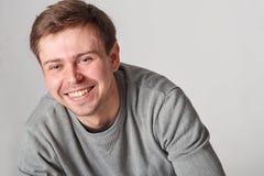 有轻的胡子的时兴的偶然微笑的年轻人,在灰色b 免版税库存照片