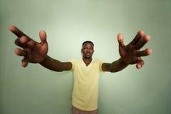 有他的胳膊的非洲人伸出身分对绿色墙壁 免版税图库摄影