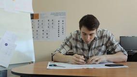 有他的脚的认为一个年轻的人在桌上,尖酸的笔,发明,他在计划开始画 影视素材