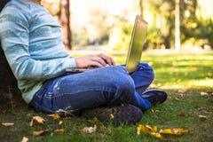 有他的膝上型计算机的年轻人在室外城市的公园 免版税库存图片