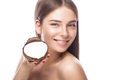有轻的自然构成的美丽的女孩和完善的皮肤用椰子在她的手上 秀丽表面 免版税库存照片