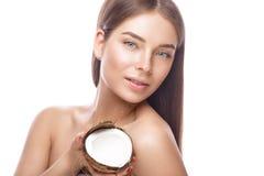 有轻的自然构成的美丽的女孩和完善的皮肤用椰子在她的手上 秀丽表面 库存照片