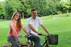 有他们的自行车的青年人在公园 免版税库存照片