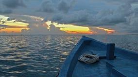 有绳索的蓝色小船在海洋在黎明 免版税库存图片