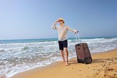 有他的行李的失去的年轻游人在海滩 免版税库存照片
