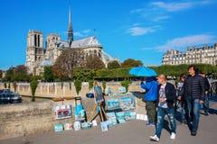 有绘画的街道艺术家与Notre Dame在背景中 免版税库存图片