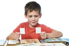有他的被隔绝的老邮票的汇集的男孩 库存图片