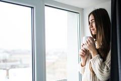 有整洁的身体的可爱的性感的妇女拿着一个杯子用热的茶或咖啡并且看窗口 库存照片