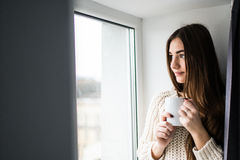 有整洁的身体的可爱的性感的妇女拿着一个杯子用热的茶或咖啡并且看窗口 免版税图库摄影