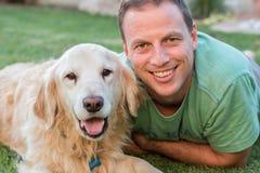 有他的金毛猎犬狗的愉快的人看照相机的两个 免版税库存照片