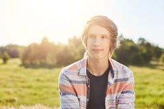 有轻的头发、穿衬衣的黑眼睛和稀薄的嘴唇的梦想的可爱的男孩坐在看在旁边wi的绿色自然背景 图库摄影
