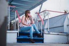 有轻的头发的坐台阶,春天,晴朗的温暖的天女孩,在太阳镜和蓝色牛仔裤 休息,看throuth太阳 免版税库存照片