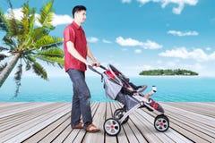 有他的婴孩的人在码头的婴儿推车的 免版税库存图片
