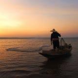 有他的去捉住的鱼的木小船的亚裔渔夫 库存照片