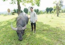 有他的水牛的农夫在他的农场 图库摄影