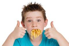 有嘴的年轻男孩有很多芯片 免版税库存图片