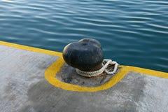 有绳索的黑老系船柱 免版税库存图片